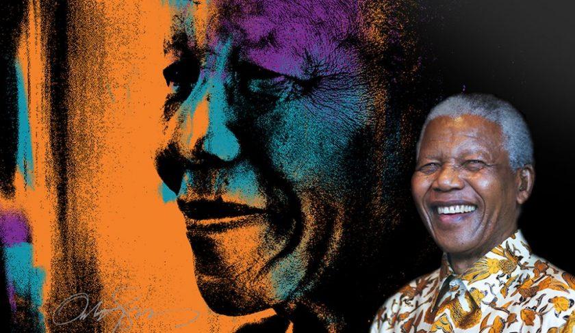 Nelson Mandella himself standing next to the orange portrait of himself